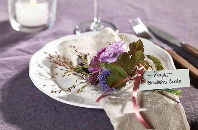 Her har vi laget et blomstersmykke til hver gjest, og merket det med navn og relasjon til den som feires.