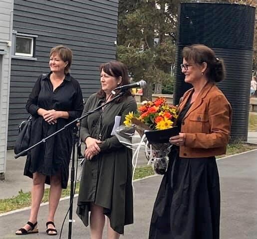 Tre kvinner står på rekke ved åpningen av en ny skole.