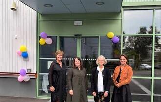 Fire kvinner står ved inngangspartiet til en flunkende ny skole