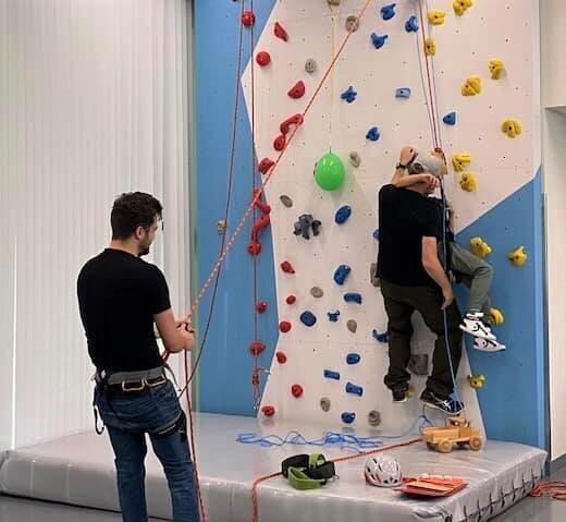 Klatrevegg: En døvblind elev blir veiledet opp veggen. Mann sikrer i forgrunnen.