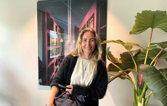 Kvinne med sort veske ved grønn plante og foran et rødt og sort bildefoto.