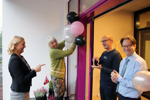 To kvinner og to menn forbereder åpning av nytt kurssenter med flagg og ballonger ved inngang.