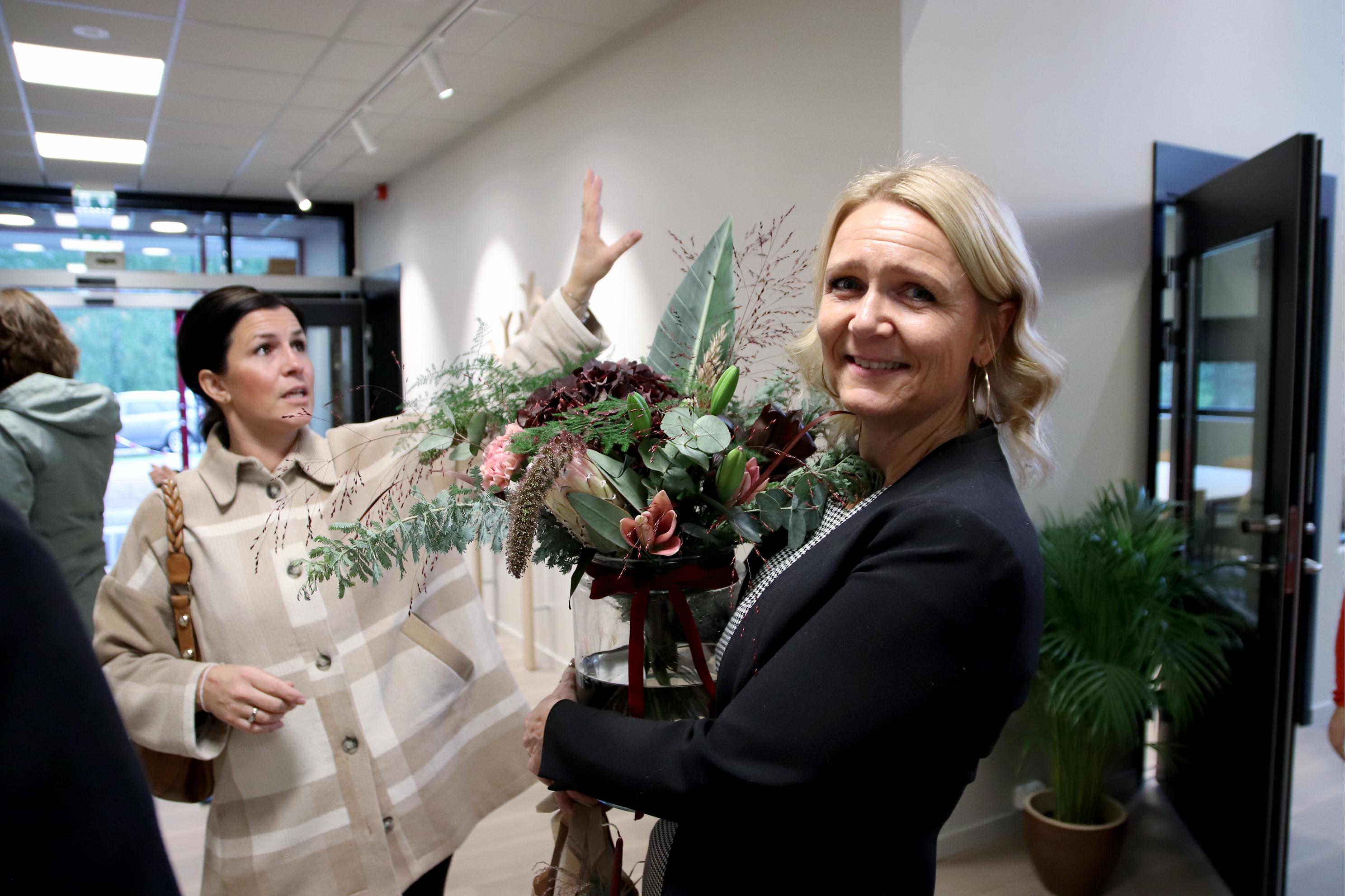 Kvinnelig leder mottar blomster på åpningen av nytt kurssenter.