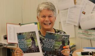 Kvinne på kontor viser smilende fram to ferske kurshefter.
